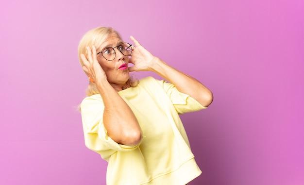 Mujer de mediana edad con la boca abierta, con aspecto horrorizado y conmocionado por un terrible error, levantando las manos a la cabeza.
