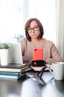 Mujer de mediana edad calificada comunicarse en línea o estudiar a distancia por teléfono en el trípode,