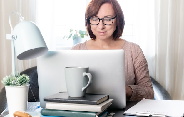 Mujer de mediana edad calificada que se comunica en línea o estudiando a distancia por computadora portátil