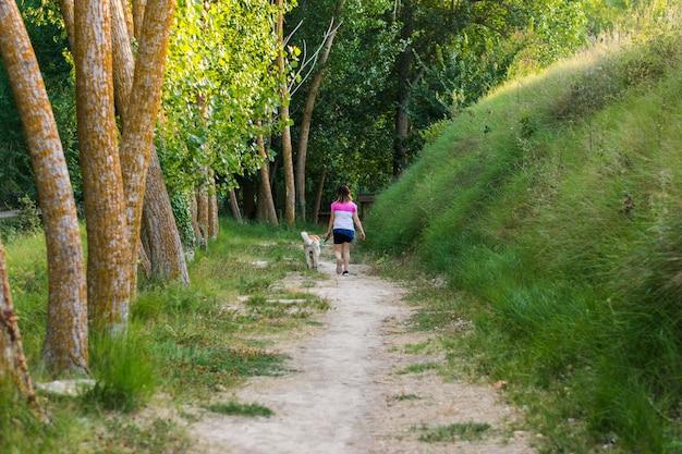 Mujer de mediana edad caminando con su perro en un sendero de montaña