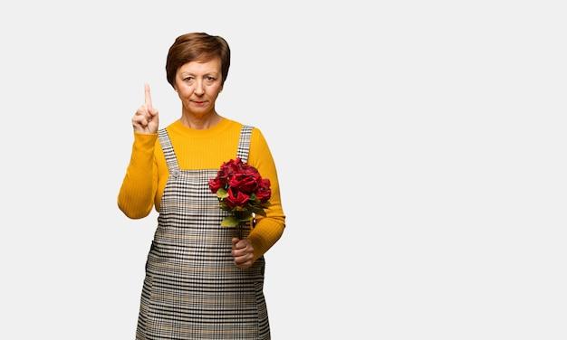 Mujer de mediana edad celebrando el día de san valentín mostrando el número uno