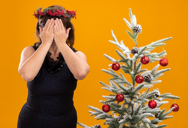 Mujer de mediana edad con corona de navidad y guirnalda de oropel alrededor del cuello de pie cerca del árbol de navidad decorado que cubre la cara con las manos aisladas en la pared naranja