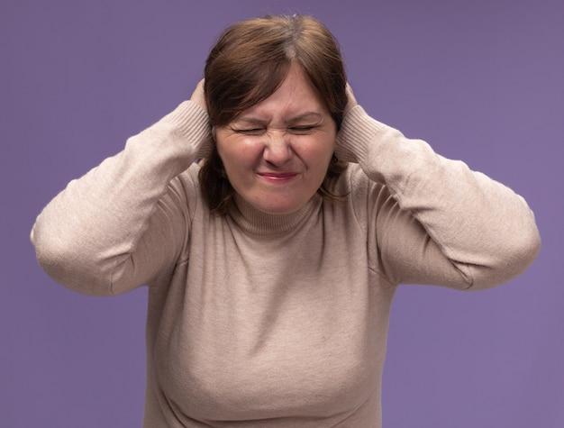 Mujer de mediana edad en cuello alto beige cerrando las orejas con las manos con expresión molesta de pie sobre la pared púrpura