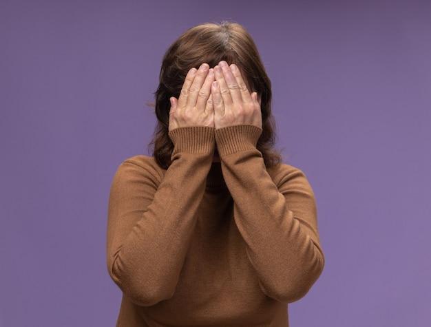 Mujer de mediana edad en cuello de tortuga marrón cerrar la cara con los brazos de pie sobre la pared púrpura