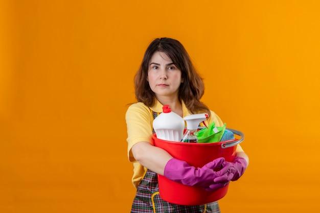 Mujer de mediana edad con delantal y guantes de goma sosteniendo un balde con herramientas de limpieza con expresión seria y segura en la cara de pie sobre la pared naranja