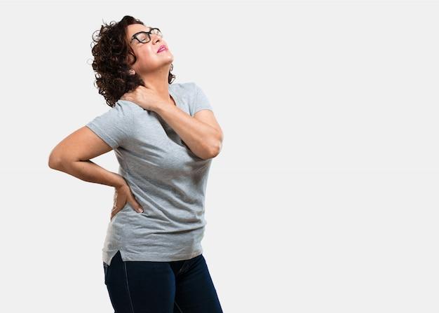 Mujer de mediana edad con dolor de espalda por estrés laboral, cansada y astuta.
