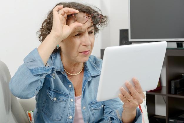 Una mujer de mediana edad con dolor en los ojos.