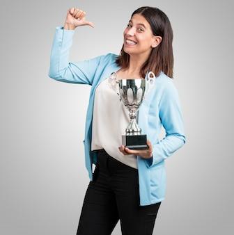 Mujer de mediana edad emocionada y enérgica, levantando un vaso después de haber logrado una victoria difícil, recompensa por el trabajo duro, segura y positiva
