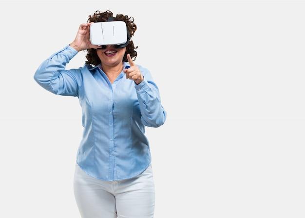 Mujer de mediana edad emocionada y entretenida, jugando con gafas de realidad virtual.