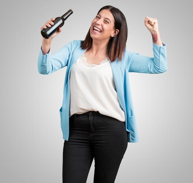 Mujer de mediana edad, feliz y divertida, sosteniendo una botella de cerveza, se siente bien después de un día intenso.
