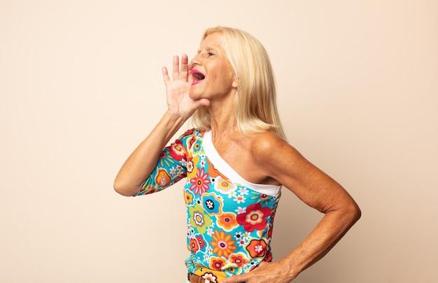 Mujer de mediana edad gritando fuerte y enojada para copiar el espacio en el costado, con la mano junto a la boca
