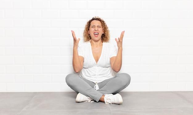 Mujer de mediana edad gritando furiosamente, sintiéndose estresada y molesta con las manos en el aire diciendo por qué yo