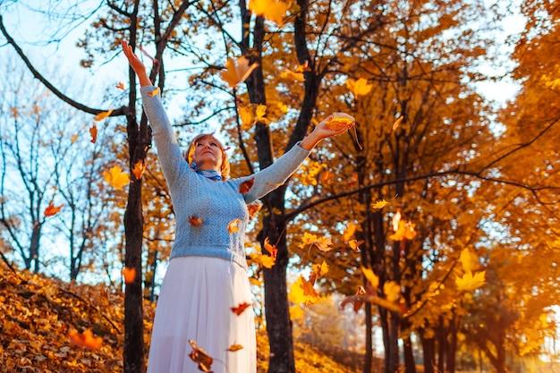 Mujer de mediana edad lanzando hojas en el bosque de otoño al atardecer. mujer mayor divirtiéndose al aire libre