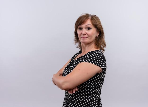 Mujer de mediana edad mirando seriamente de pie con postura cerrada en la pared blanca aislada con espacio de copia