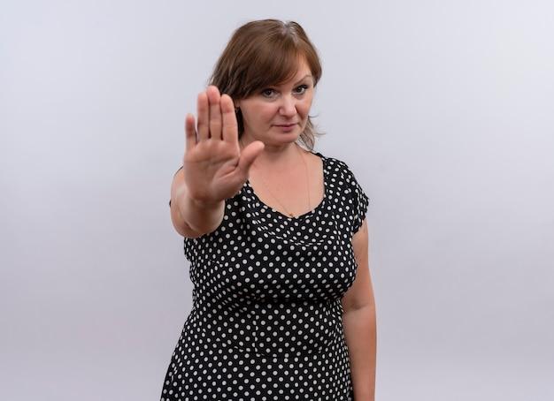 Mujer de mediana edad mirando seriamente que muestra la señal de pare con la mano en la pared blanca aislada
