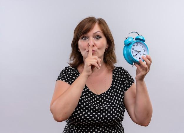 Mujer de mediana edad mirando seriamente sosteniendo reloj despertador y gesticulando silencio en una pared blanca aislada con espacio de copia