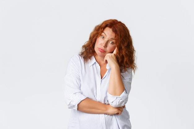 Mujer de mediana edad molesta y molesta, cansada con cabello rojo que parece agotada y harta, apoyándose en la mano y mirando a la cámara escéptica, escuchando conversaciones sin sentido, fondo blanco.