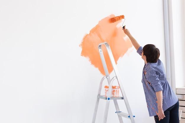 Mujer de mediana edad muy sonriente pintando la pared interior de la casa con rodillo de pintura.