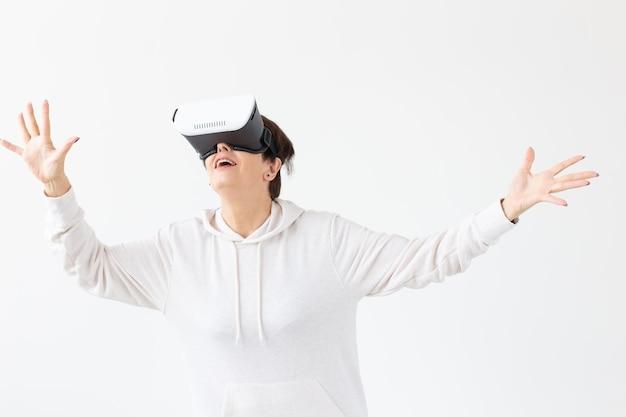 Mujer de mediana edad no identificada con un suéter ligero juega un juego en 3d con gafas de realidad virtual en una pared blanca. concepto de alta tecnología para personas mayores.