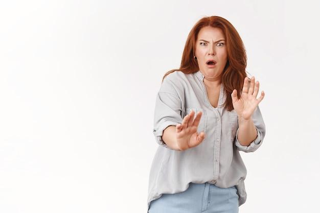 Mujer de mediana edad pelirroja encogida disgustada muestra aversión paso atrás renuente levantar manos defensivas muecas disgustado horrible olor terrible, pared blanca