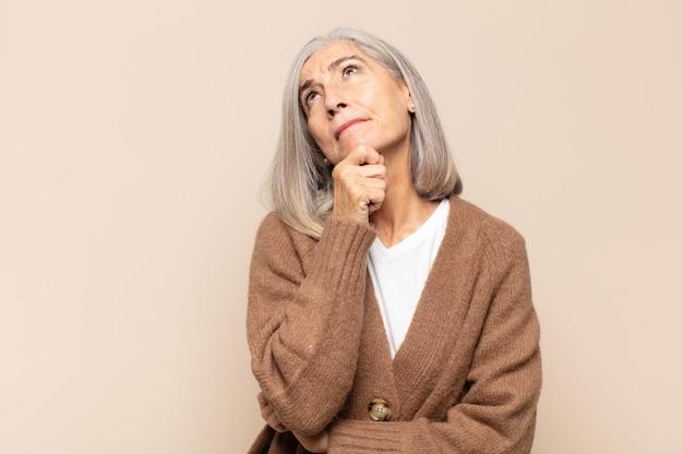 Mujer de mediana edad pensando, sintiéndose dudosa y confundida, con diferentes opciones, preguntándose qué decisión tomar