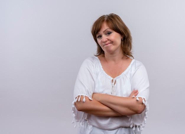 Mujer de mediana edad pensativa de pie con postura cerrada en pared blanca aislada