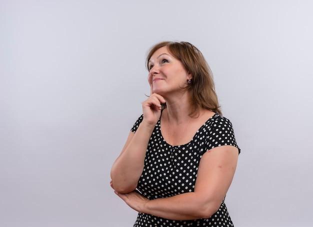Mujer de mediana edad pensativa poniendo el dedo en la cara en la pared blanca aislada con espacio de copia