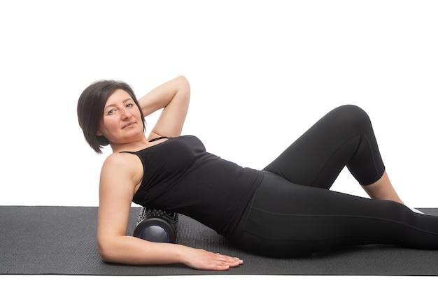 Una mujer de mediana edad con piel flácida sobre una colchoneta de gimnasia con rodillo miofascial hace un ejercicio sobre su espalda en una pared blanca