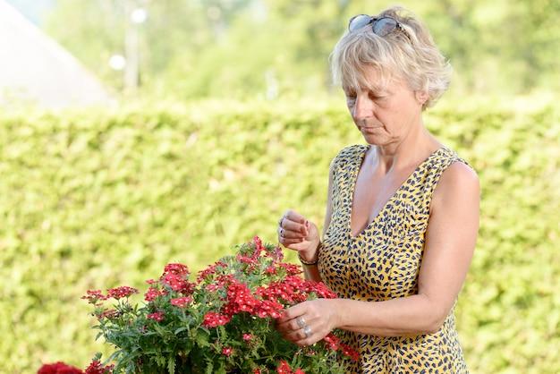 Una mujer de mediana edad con una planta con flores en el jardín.