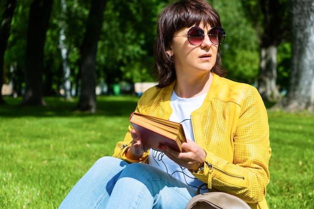 Mujer de mediana edad positiva en gafas de sol se sienta en un campo en un parque y lee un libro en un cálido día de verano soleado