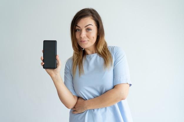 Mujer de mediana edad positiva que muestra la pantalla del teléfono inteligente y mirando a cámara.