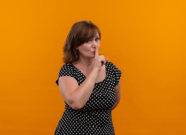 Mujer de mediana edad que mira seriamente que gesticula el silencio en la pared anaranjada aislada con el espacio de la copia