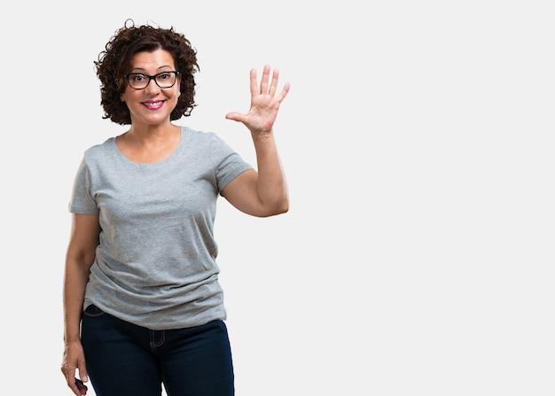 Mujer de mediana edad que muestra el número cinco, símbolo de contar, concepto de matemáticas