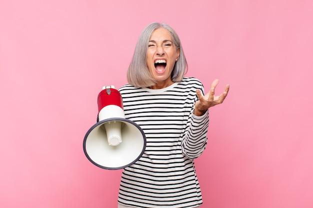 Mujer de mediana edad que parece enojada, molesta y frustrada gritando wtf o qué te pasa con un megáfono