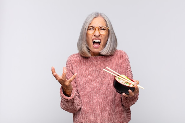Mujer de mediana edad que parece enojado, molesto y frustrado gritando wtf. concepto de comida asiática