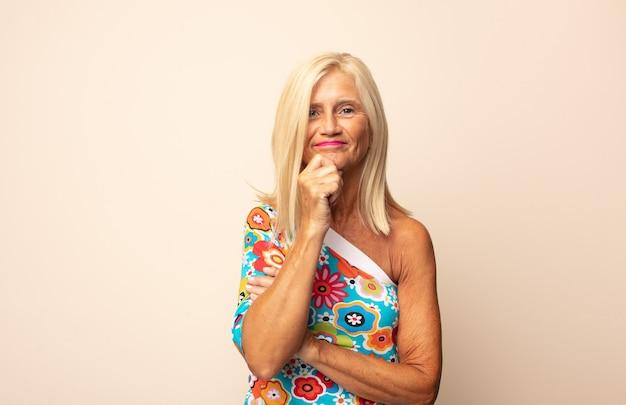 Mujer de mediana edad que parece feliz y sonriente con la mano en la barbilla, preguntándose o haciendo una pregunta, comparando opciones