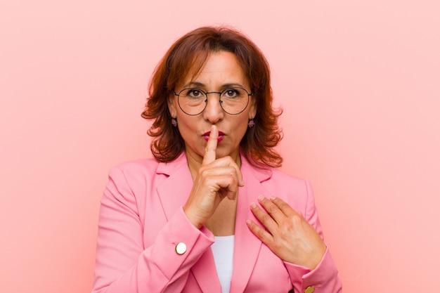 Mujer de mediana edad que parece seria y cruzada con el dedo presionado contra los labios exigiendo silencio o silencio, guardando un secreto