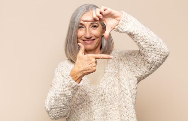 Mujer de mediana edad que se siente feliz, amigable y positiva, sonriendo y haciendo un retrato o marco de fotos con las manos