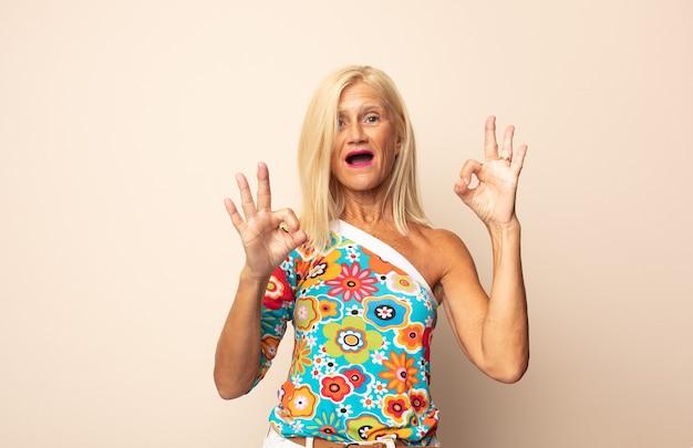 Mujer de mediana edad que se siente feliz, asombrada, satisfecha y sorprendida, mostrando gestos de aprobación y pulgar hacia arriba, sonriendo