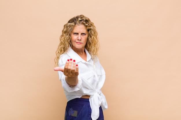 Mujer de mediana edad que se siente feliz, exitosa y segura, enfrenta un desafío y dice ¡adelante! o dándote la bienvenida