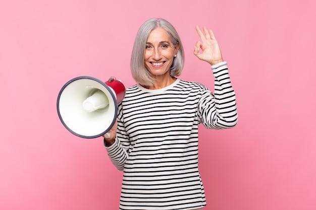 Mujer de mediana edad que se siente feliz, relajada y satisfecha, mostrando aprobación con un gesto aceptable, sonriendo con un megáfono