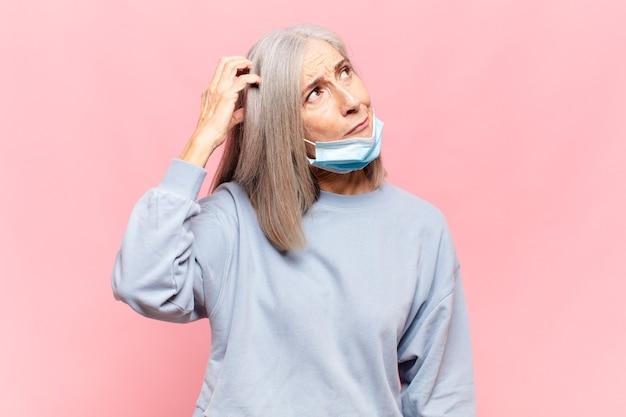 Mujer de mediana edad que se siente perpleja y confundida, rascándose la cabeza y mirando hacia un lado