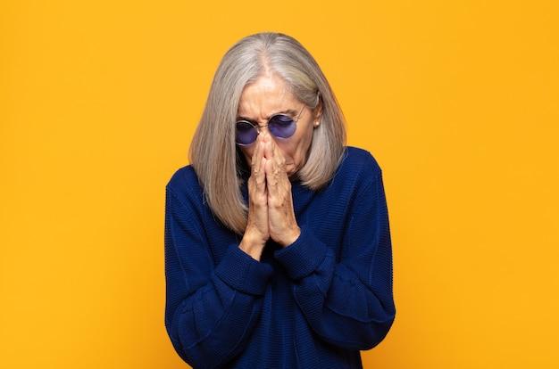 Mujer de mediana edad que se siente preocupada, esperanzada y religiosa, orando fielmente con las palmas presionadas, pidiendo perdón