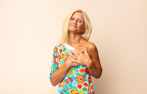 Mujer de mediana edad que se siente romántica, feliz y enamorada, sonriendo alegremente y tomados de la mano cerca del corazón