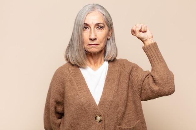 Mujer de mediana edad que se siente seria, fuerte y rebelde, levanta el puño, protesta o lucha por la revolución