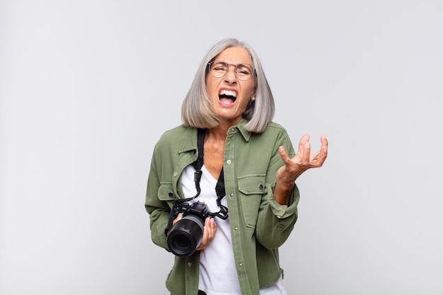 Mujer de mediana edad que se ve enojada, molesta y frustrada gritando wtf o qué te pasa. concepto de fotógrafo