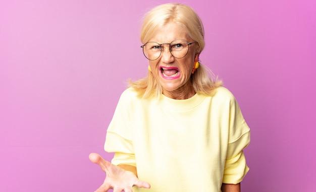 Mujer de mediana edad que se ve enojada, molesta y frustrada gritando wtf o qué te pasa