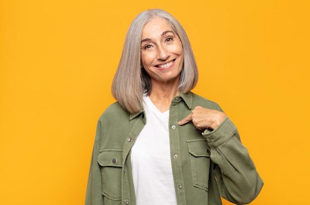 Mujer de mediana edad que se ve feliz, orgullosa y sorprendida, alegremente apuntando a sí misma, sintiéndose segura y elevada