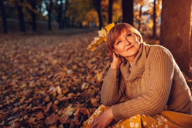 Mujer de mediana edad con ramo de hojas de arce señora disfrutando de la naturaleza de otoño