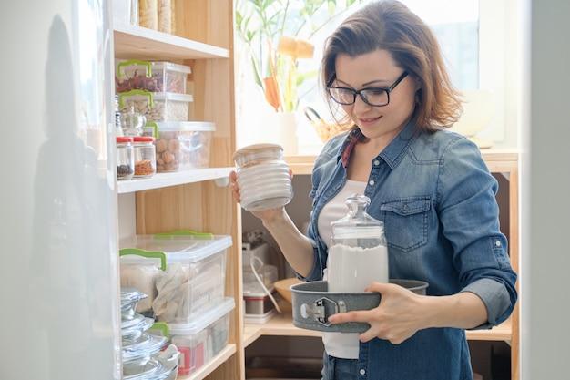 Mujer de mediana edad recogiendo alimentos del gabinete de almacenamiento en la cocina
